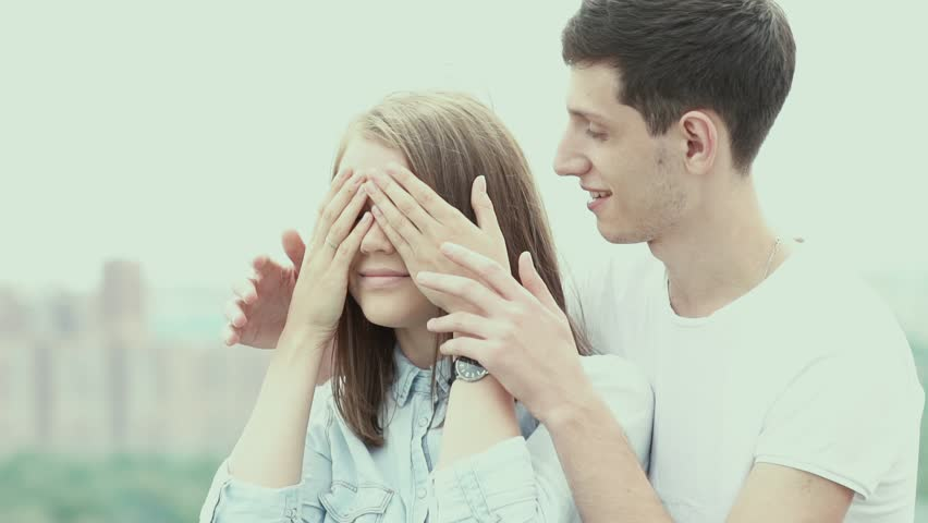 Surprise with closed eyes. Romantic man gave his girlfriend a surprise. Couple in love. The girl closed her eyes with their hands. Surprise for lover. Happiness. Love. The girl smiles. Couple on roof