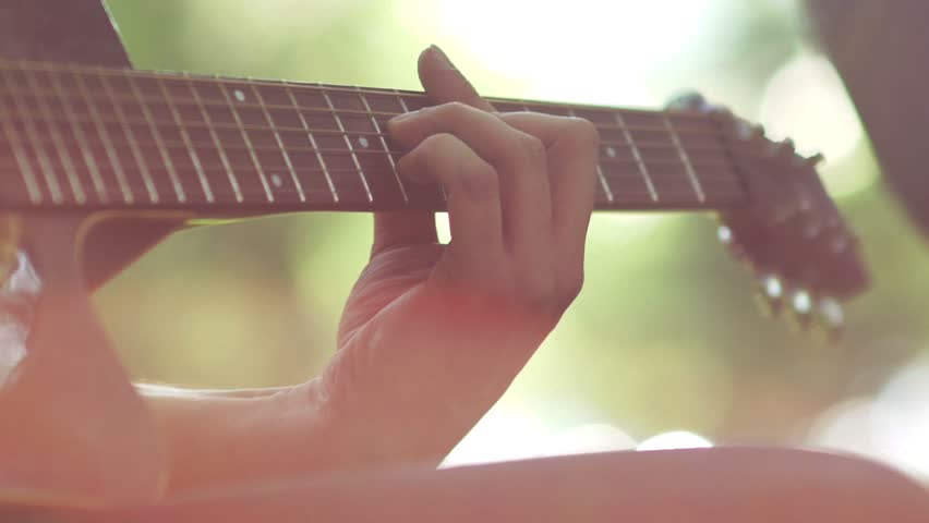 Slow motion. Close-up of guitar playing. Guitarist hits the strings of the guitar. Skill. Playing a musical instrument. Stringed Musical Instruments. Black guitar with abrasions. Old Guitar.