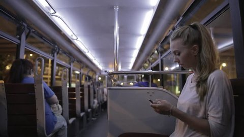 Passengers sitting inside of double-decker tram in the evening Hong Kong, China. Portrait of young attractive woman citting inside of tram, using and looking into her smartphone.
