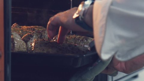 Slowmotion. Cook put the pan with the meat in the oven. Hands male chef in uniform. Cooking meat in the oven. A delicious roast beef. a tasty piece pork is cooked in the oven.