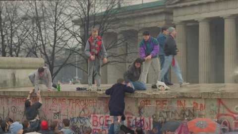 day people climbing top Berlin Wall, celebrating near Berlin Wall, fall Berlin Wall, historical footage