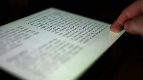 Close-up of a finger turning the pages of a digital ebook reader.  Extreme shallow DOF