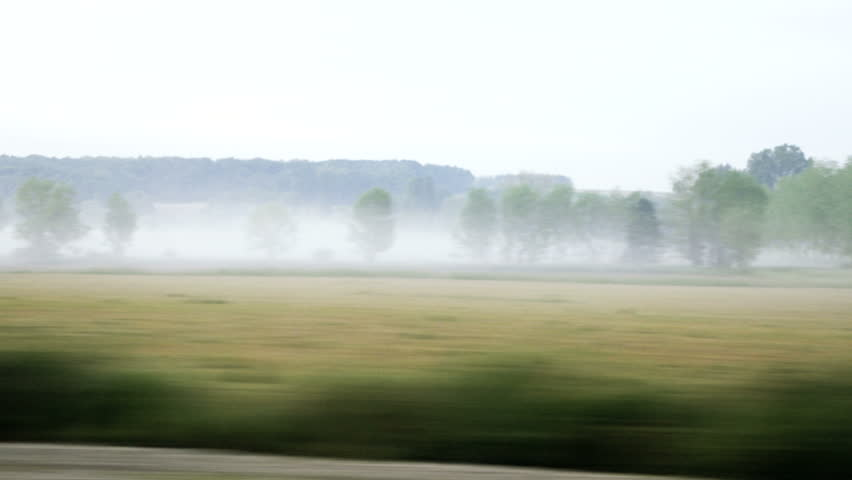 Foggy morning mist evening as see from fast tgv train traveling in France admiring the hills and forest and agricultural fields