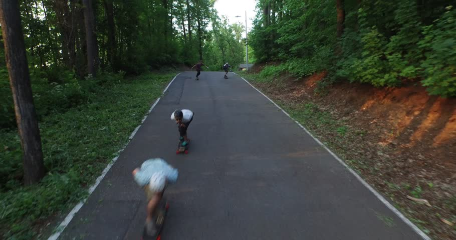 Mixed group of teenaged longboarders racing each other downhill on a mountain road longboard on road