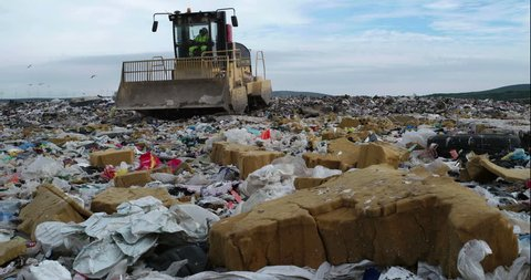 Bulldozer flattening garbage in landfill waste site