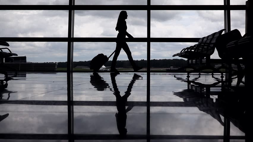 Female traveller silhouette, woman go against terminal window with trolley case, slow motion. Empty departure hall, full height passenger, polished floor reflect shadow contour. Cloudy sky outside   Shutterstock HD Video #20833213