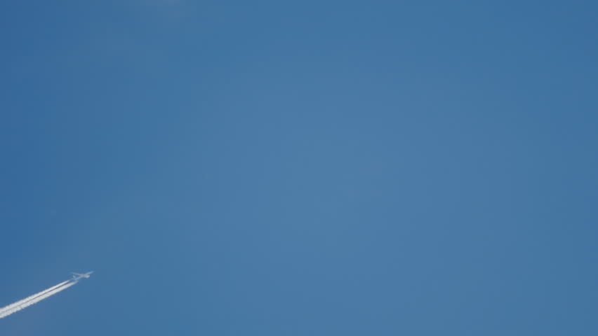 Contrails in the blue sky. Airplane flying high. Slow motion