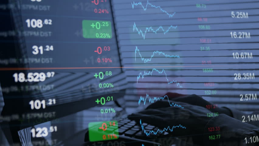 Financial background, online trading concept: stock market trading board, abstract tickers, stock quotes, chart. On the background a businessman trader working on the computer, typing on the keyboard. | Shutterstock HD Video #20843014