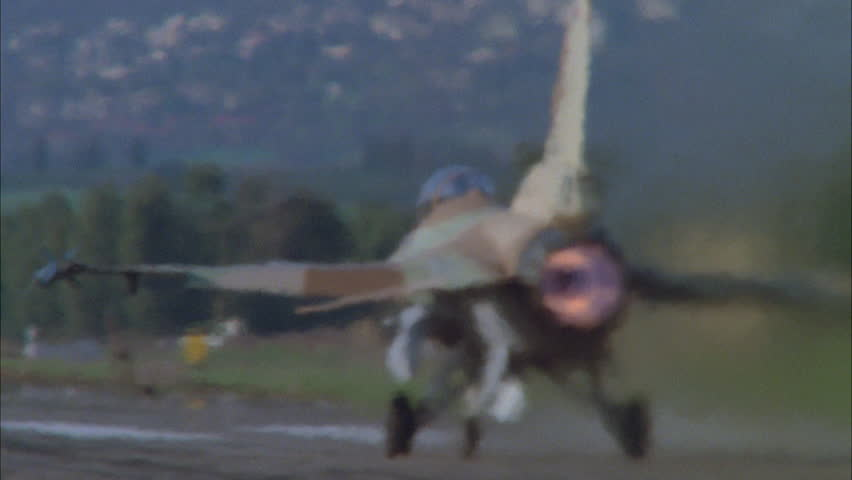 day F 16 Falcon fighter jet, away rural runway, see heat halation's from afterburner Rack focus parked Falcon, rear view, 1st takes Tilt up 1st Falcon gains altitude playback,