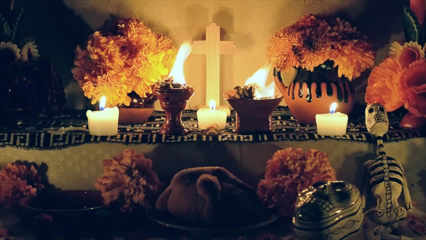 "Day of the dead offering altar with ""pan de muerto"", cempasuchil flowers, burning copal and candles. Essential part of Day of the Dead festivities in Mexico."