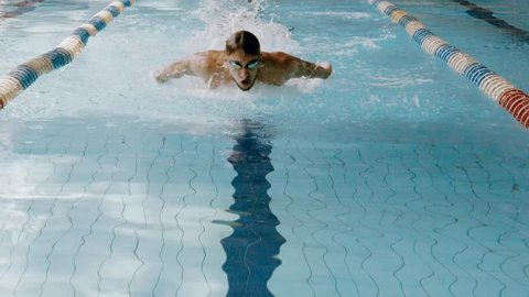 Slow motion view of swimming. Swimmer in action in waterpool with blue water at sunny day.