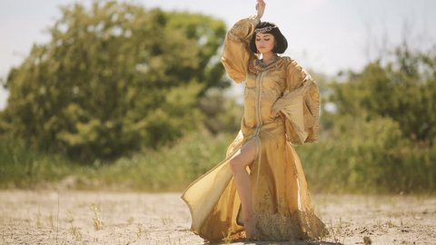Fashion stylish beauty woman with black short haircut and professional make-up of Cleopatra. Girl dancing in full lenght in golden dress outdoors in desert