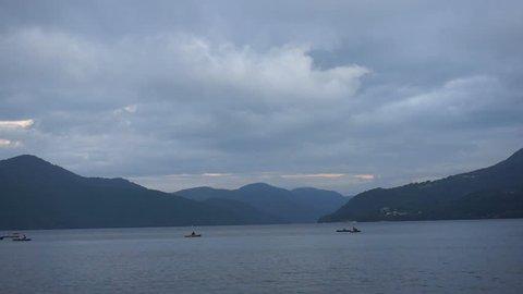Mountain lake on dusk with fishing boats in the distance. Lake Ashi, Hakone, Japan