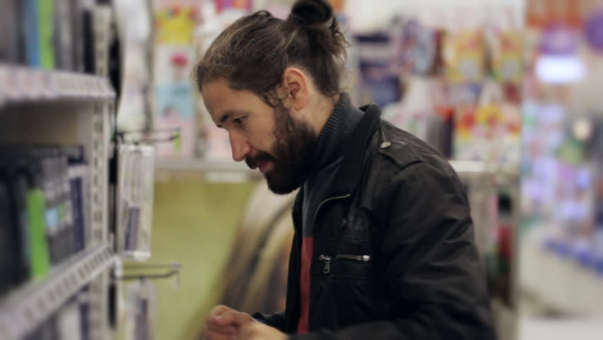 Portrait of men with beard and long hair selecting a body spray in supermarket. | Shutterstock HD Video #20904592