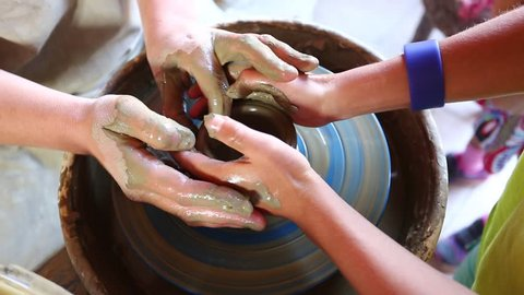 Female potter craftsman helps the learner to work on pottery wheel
