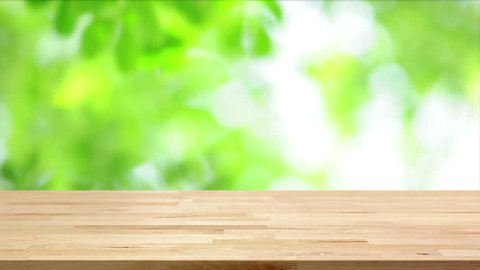 Wood table top on blur moving natural green leaf background