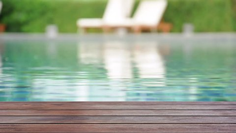 Wooden deck on rippled swimming pool water background - can be used for display or montage your products on top