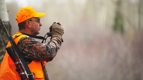 Elk Hunting in a Colorado wilderness area during October snowstorm. Hunter raises binoculars searching for game.