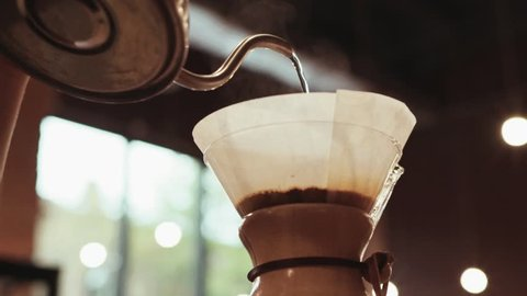 Close up of a barista making hand brewed coffee. Adding grinded coffee and pouring hot water. Baristas portrait. Inside shooting. Cafe atmosphere. Cafe activities. Restaurant activities.