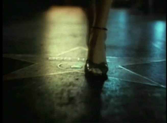 Close-up of woman in high heels strolling on Walk of Fame