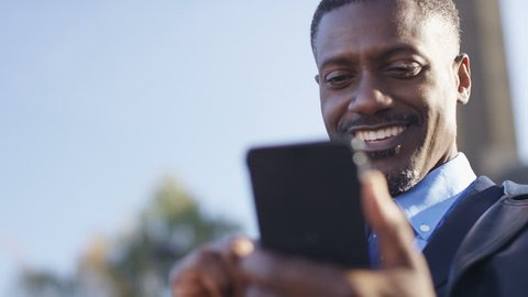 4K Attractive business man using his phone outdoors, in slow motion
