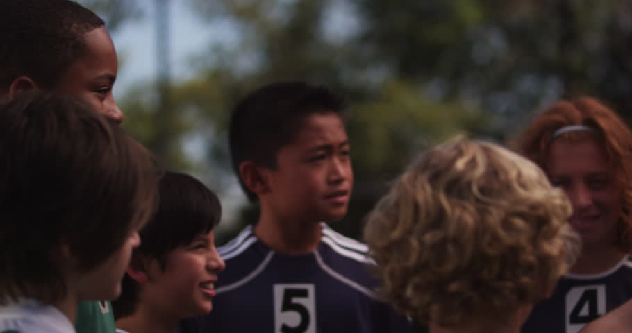 An enthusiastic coach gives his diverse team of youth league players a pep talk before sending them out onto the field. Version 5.