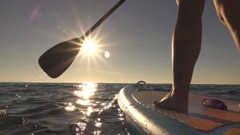 SLOW MOTION, CLOSE UP: Woman standing firmly on inflatable SUP board and paddling. Hands pushing and pulling the paddle through shining water surface and propelling paddleboard on sunny morning