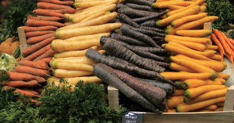 Tilt up view of a display of organic vegetables roots at a food market: carrots, black carrots, turnips