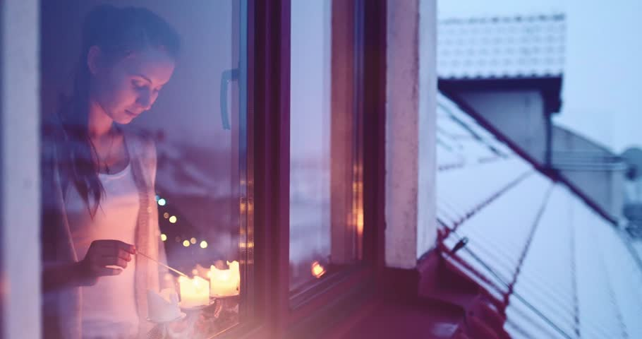 Young Woman lighting Advent Candles on the Window, Winter Cozy Evening. 4K DCi SLOW MOTION 120 fps. Winter Holidays concept. Christmas Traditions. View from outside the window. Snow-covered house.