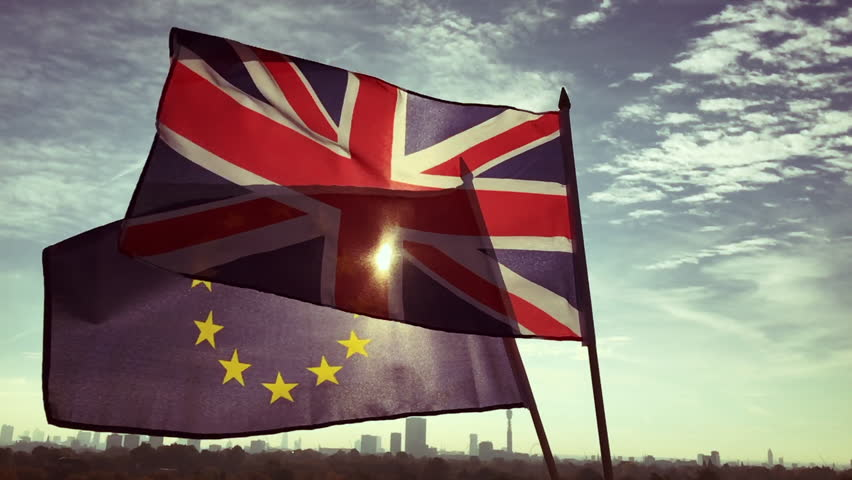 European Union and British Union Jack flag flying together in front of a sunrise skyline of London, England