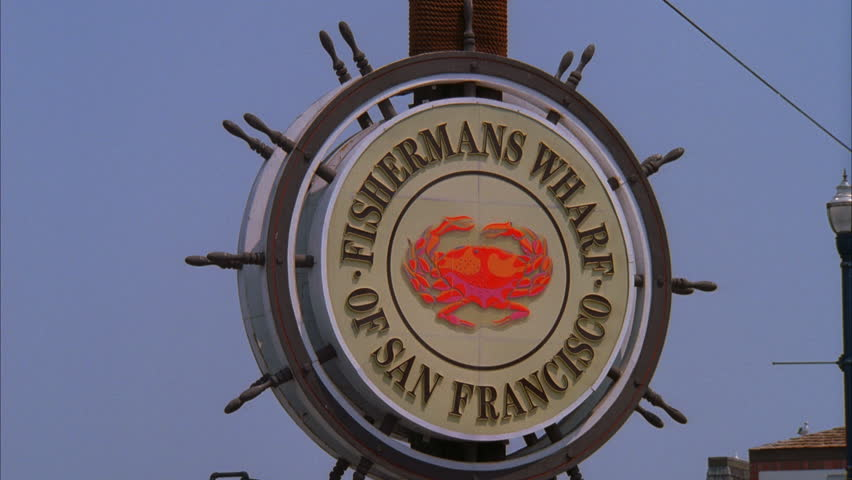 day Tilt up from seagull sitting wood pole round FISHERMAN'S WHARF OF SAN FRANCISCO sign with crab picture