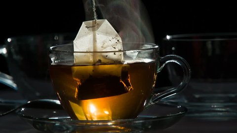 Tea Bag in a Transparent Cup. Teabag falls in a transparent cup with hot water on a dark background.  Water is painted in the color of tea. Shooting at a rate of 240fps.