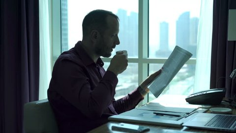 Young businessman reading newspaper and drinking coffee sitting by desk in office, 4k