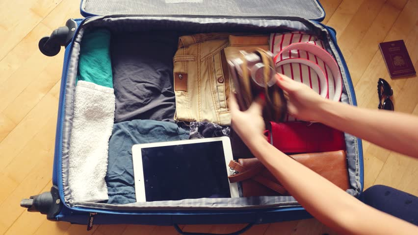 Woman's hands are packing suitcase for a journey. Dreams about travel. 3840x2160 | Shutterstock HD Video #21081439