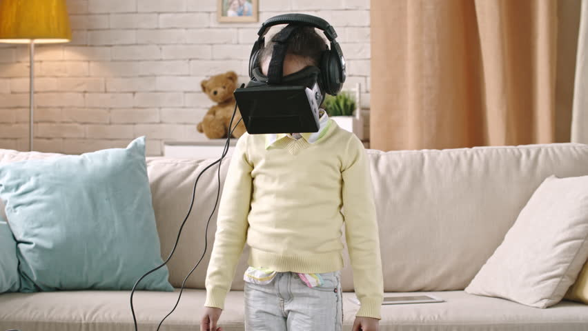 90760c3e42c6 Girl in virtual-reality headset standing in the living room and looking  upside and down