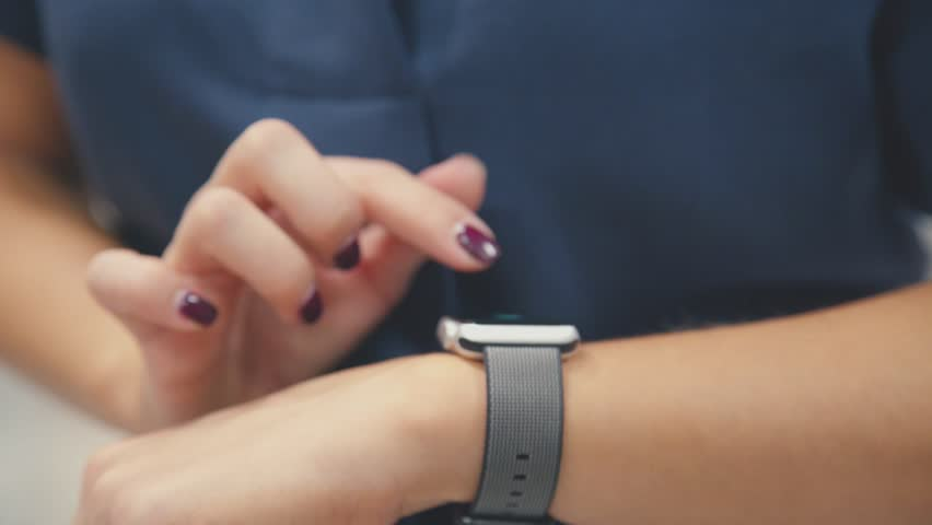 Woman using her smartwatch touchscreen wearable technology device. Young woman trying new smart watch. Smart watch. Woman Using Smart Watch and Smart Phone. Closeup. Smart watch on female wrist