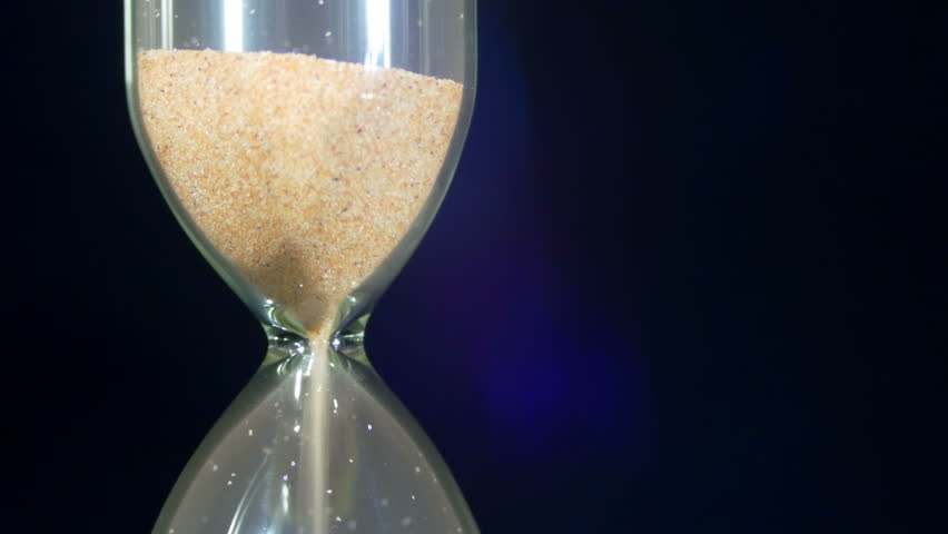 Hourglass on a black background, the sand falls inside. Close Up. Running Sand in the Sandglass. Egg timer emptying against a black background. Sands move through hour glass. Ultra HD, 4K, 3840 x | Shutterstock HD Video #21098644