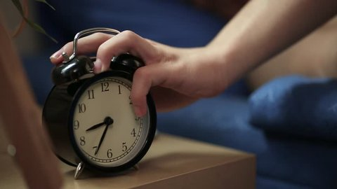Teenage boy woken by alarm clock turns off alarm before hiding under his blanket