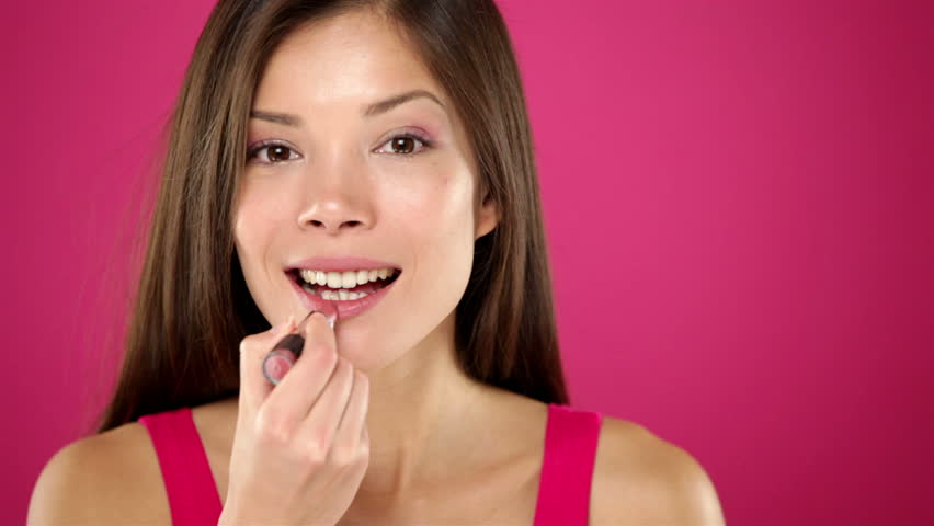 Makeup woman putting lipstick smiling happy on pink red background. Beautiful young mixed race Asian / Caucasian female model.