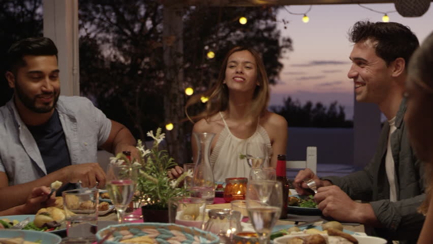 Friends laughing at a dinner party on a roof terrace, Ibiza, shot on R3D