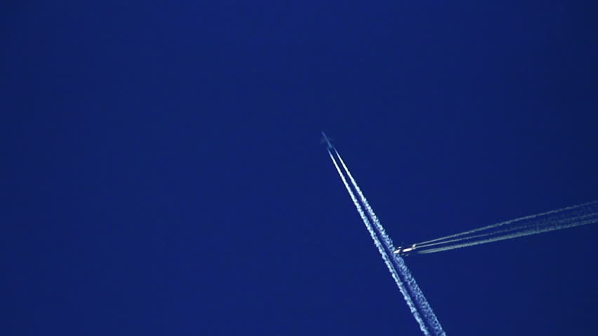 Plane trails crossing against clear blue sky