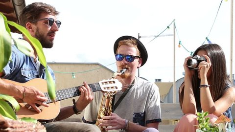 Two charismatic guys playing music with guitar and saxophone at the party while girl taking photos of them and laughing