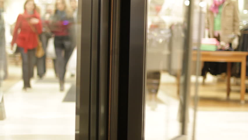 Revolving door with customers at clothes store