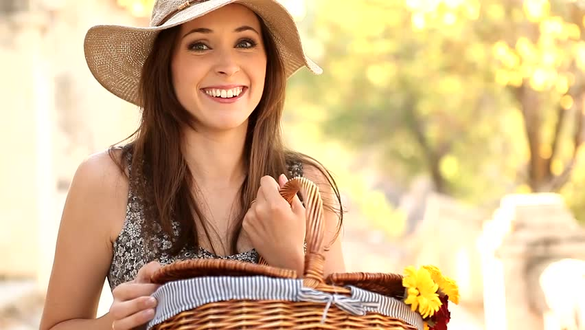 Young curious woman looking into her picnic basket