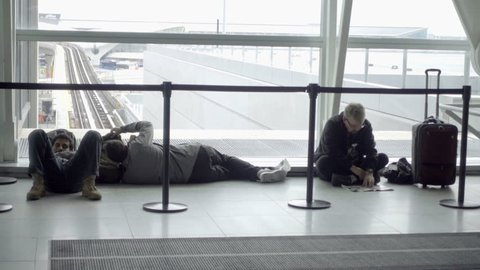 NEW YORK - SEPTEMBER 29, 2016: Travelers Sleeping And Lying On Floor In JFK Airport in NY. John F Kennedy is one of the northeast's most popular and busy airports.