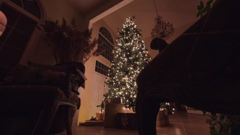 Big Christmas tree with glowing lights, ornaments, and presents in a beautifully decorated home. Side dolly shot.