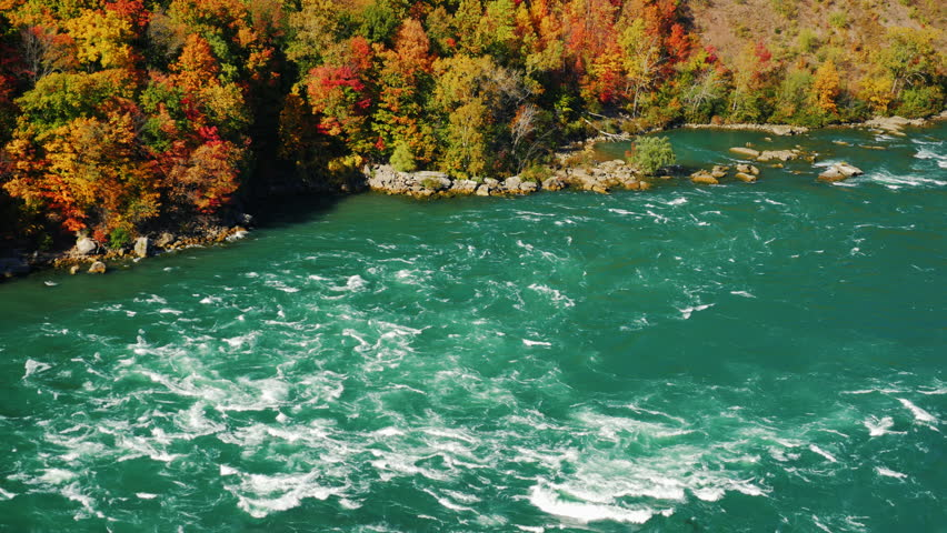 The flow of the river Niagara rapids. Against the background of colorful autumn forest. The river divides the US and Canada, a popular tourist route New York