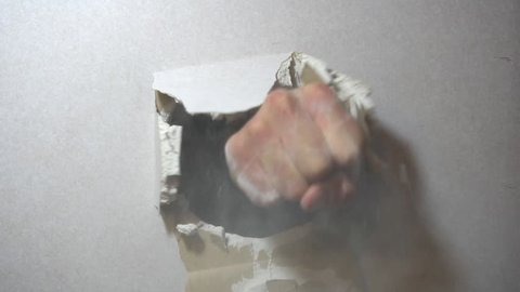 aggression concept, wall is broken through by a fist