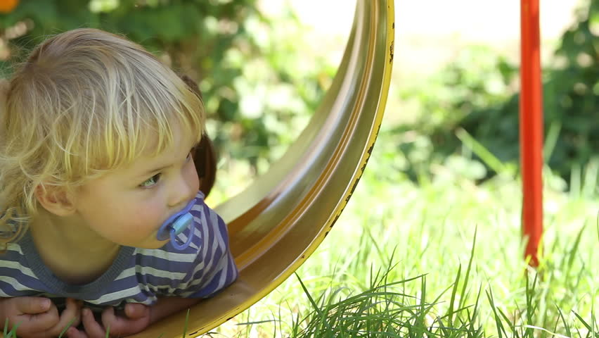 Cute and carefree toddler swinging in barrel swing (jungle gym) - thoughtfully looks around at this new experience!
