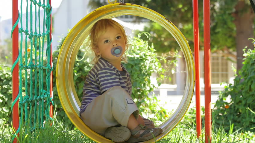 Carefree toddler swinging in barrel swing (jungle gym) - thoughtfully enjoying this new experience!